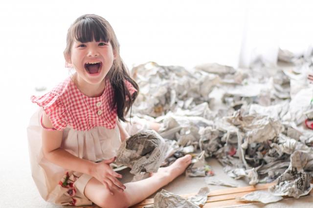 新聞紙で遊ぶ子ども